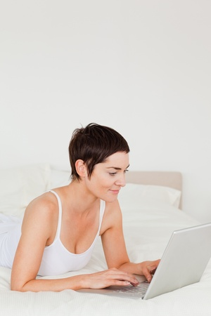 Portrait of a young woman using a laptop in her bedroom photo