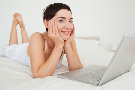 Charming woman using a laptop in her bedroom photo
