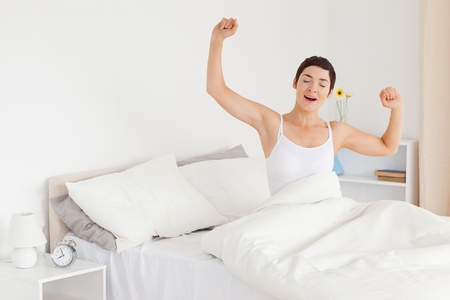 Woman stretching her arms to wake up photo
