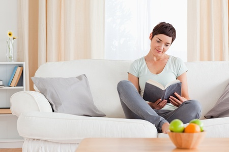 Lovely woman reading a book in her living room Stock Photo - 10780423