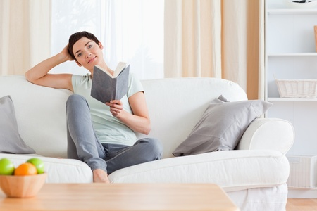 Cute brunette reading a book in her living room photo