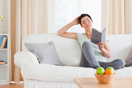 Charming woman reading a book in her living room photo