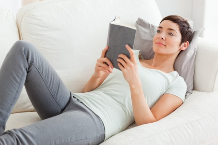 Beautiful brunette reading a book in her living room photo