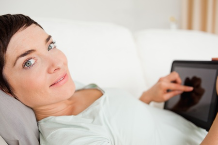 Smiling woman using a tablet computer while looking at the camera photo