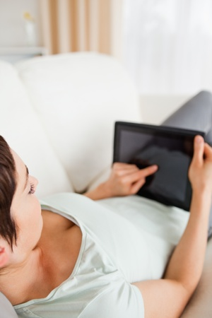 Top view of a woman using a tablet computer in her living room photo