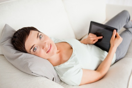 Cute woman using a tablet computer in her living room photo