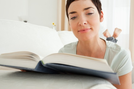 Close up of a short-haired woman reading a book lying on her belly Stock Photo - 10780372