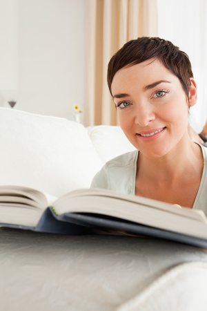 Portrait of a short-haired woman with a book looking at the camera photo