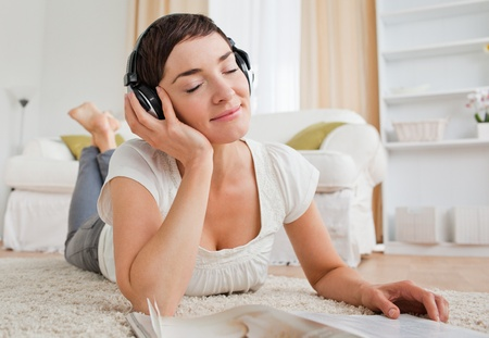 Delighted woman with a magazine enjoying some music while lying on a carpet photo