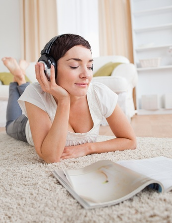 Portrait of a cute woman reading a magazine while enjoying some music in her living room photo