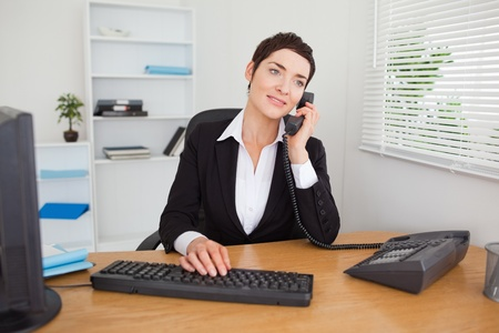 Secretary answering the phone in her offic photo