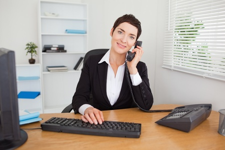 Young secretary answering the phone in her office photo