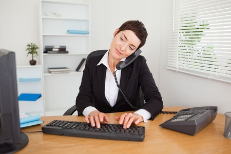 reception desk: Active secretary answering the phone in her office