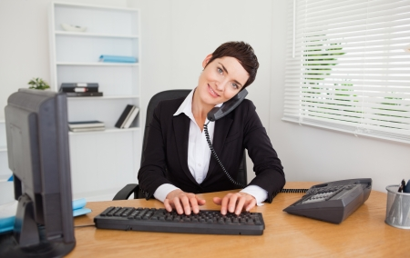 Professional secretary answering the phone in her office photo
