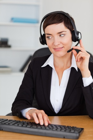 Portrait of a professional secretary calling with a headset in her office photo