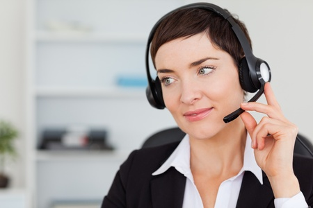Close up of a secretary calling with a headset in her office photo