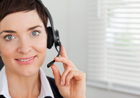 Close up of a smiling secretary calling with a headset in her office photo