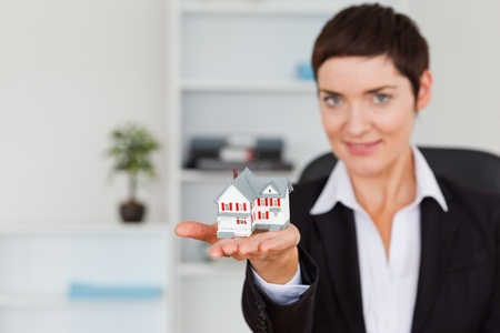 Brunette showing a house miniature with the camera focus on th object photo