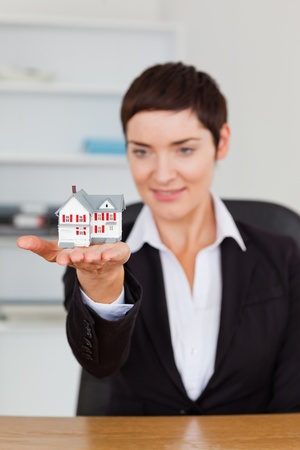 Portrait of a brunette showing a house miniature in her office photo