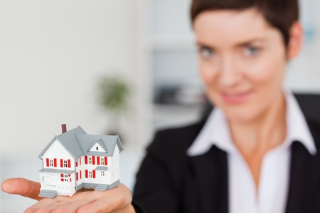 Close up of a brunette showing a miniature house with the camera focus on the object photo