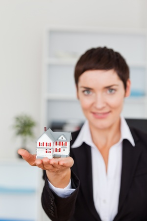 Portrait of a woman showing a miniature house with the camera focus on the object photo