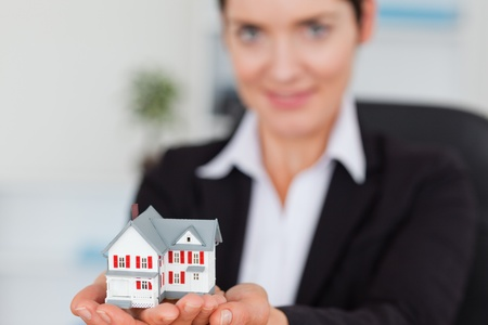 Businesswoman holding a miniature house with the camera focus on the object photo