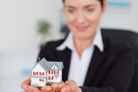 Smiling businesswoman holding a miniature house with the camera focus on the objecty photo