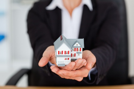 Feminine hands holding a miniature house in an office photo