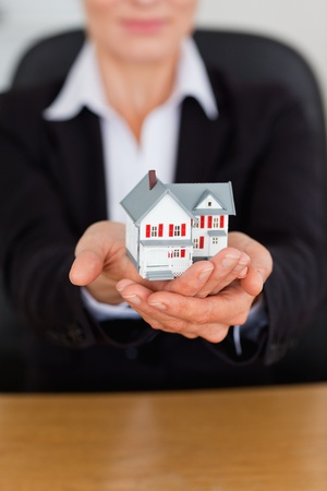 Portrait of feminine hands holding a miniature house in an office photo