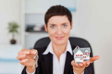 Woman showing a miniature house and a key with the camera focus on the objects Stock Photo - 10780380