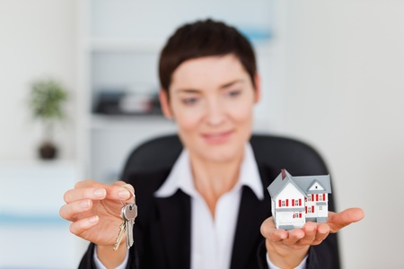 Smiling woman showing a miniature house and a key with the camera focus on te objects Stock Photo - 10791367