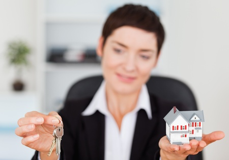 Businesswoman showing a house miniature and a key in her office photo