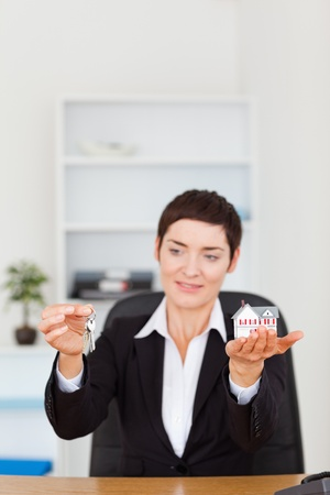 Portrait of a woman showing a miniature house and a key in her office Stock Photo - 10790292