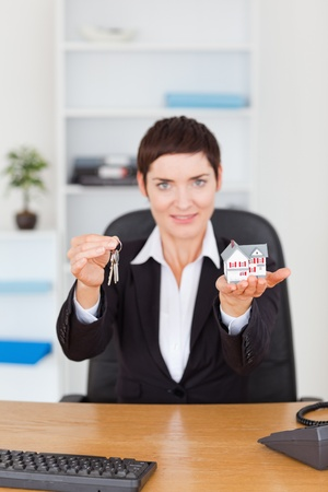 Portrait of a businesswoman showing a miniature house and a key in her office Stock Photo - 10779877