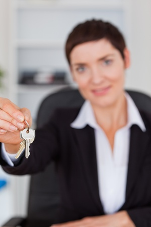 Portrait of a businesswoman showing keys with the camera focus on the keys photo