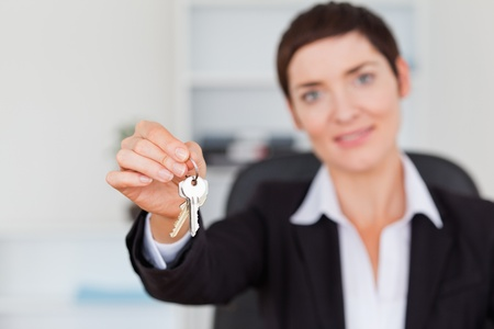 Businesswoman showing keys with the camera focus on the keys photo