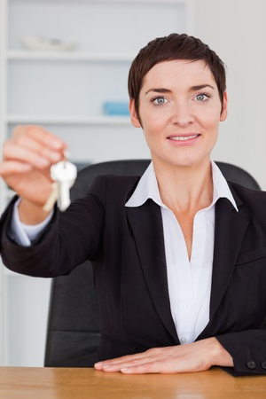 Portrait of a smiling secretary showing keys in her office photo