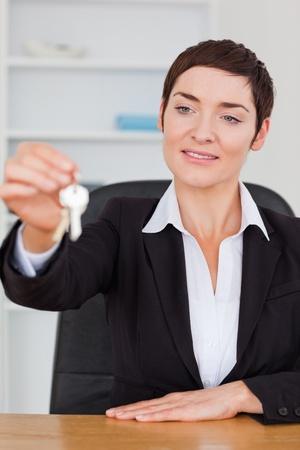 Portrait of a cute secretary showing keys in her office photo
