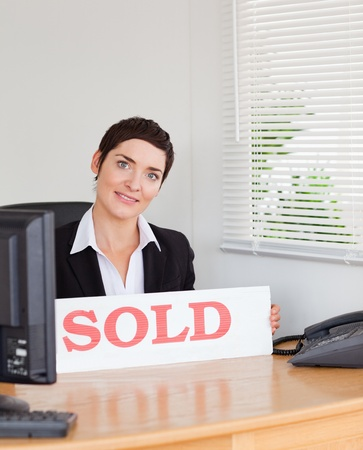 Charming real estate agent with a sold panel in her office photo