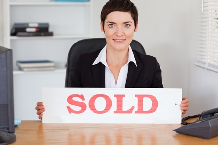 Cute real estate agent with a sold panel in her office photo