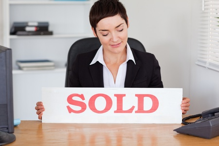Real estate agent looking at a sold panel in her office photo