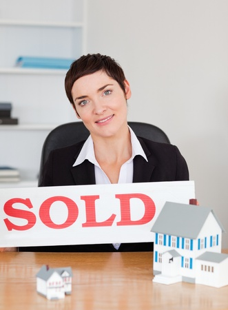 Real estate agent with a sold panel and houses miniatures in her office photo