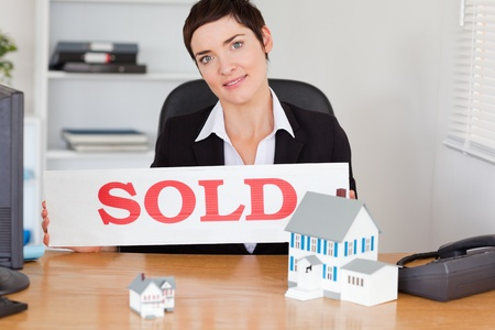 Female real estate agent with a sold panel and houses miniatures in her office photo