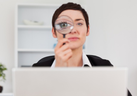 Office worker looking through  a magnifying glass in her office Stock Photo - 10787132