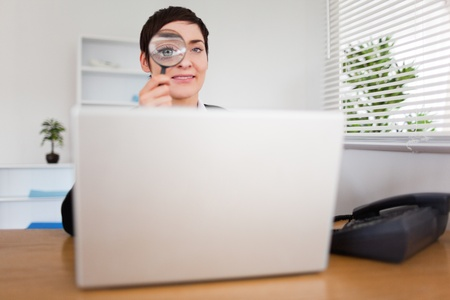 Businesswoman looking through  a magnifying glass to look at her laptop Stock Photo - 10791711