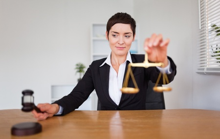 Young woman with a gavel and the justice scale in her office Stock Photo - 10791668