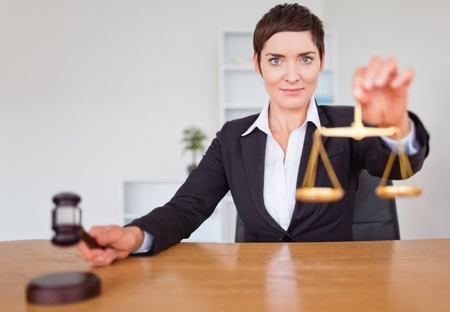 Serious woman with a gavel and the justice scale in her office Stock Photo - 10788413
