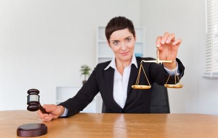 acomodador: Mujer profesional con un martillo y la escala de la justicia con el enfoque de la c�mara en los objetos Foto de archivo