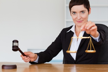 Judge with a gavel and the justice scale in her office Stock Photo - 10786760