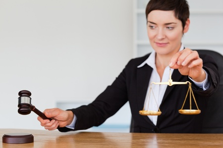 Young judge with a gavel and the justice scale in her office Stock Photo - 10784553